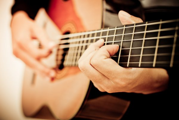 Man playing guitar, focus on strings and hands