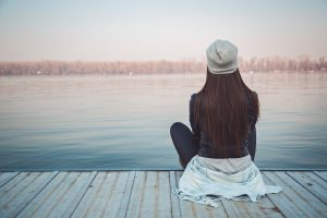 Woman sitting quietly on wooden pier, looking out at lake