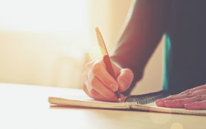 Man siting at desk, writing in journal, expressing himself