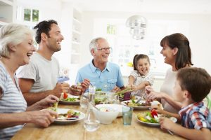 Family of 4 with grandparents sharing a meal together at home