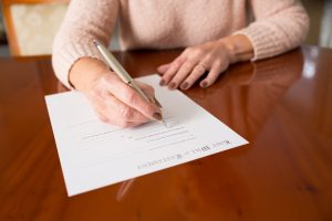 Woman in pink sweater sitting at table, signing a legal will