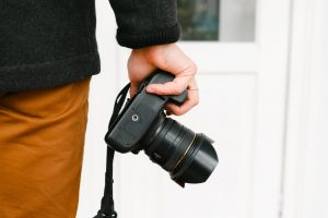 Man holding camera in right hand, held by his thigh