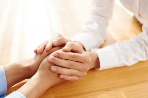 Two people holding hands in comfort