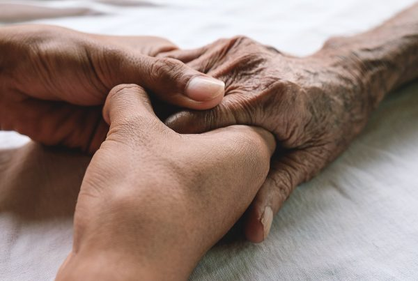 Focus on hands resting on bed, young person holding elderly person's hand
