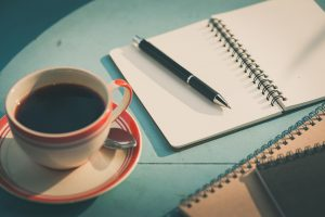 Open notebook with coffee and pen on blue table