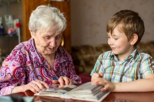 Great-grandmother sitting at table, looking at old photo album with grandson