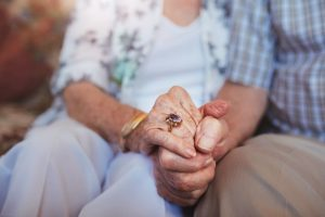Focused on clasped hands of an elderly husband and wife