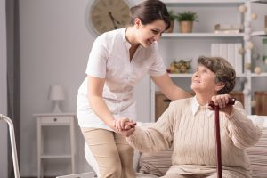 Hospice nurse helping older woman stand