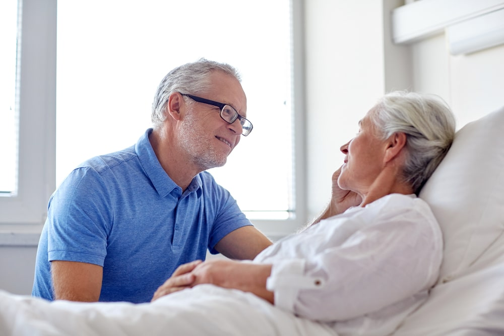 Husband talking to wife as she lies in hospital bed