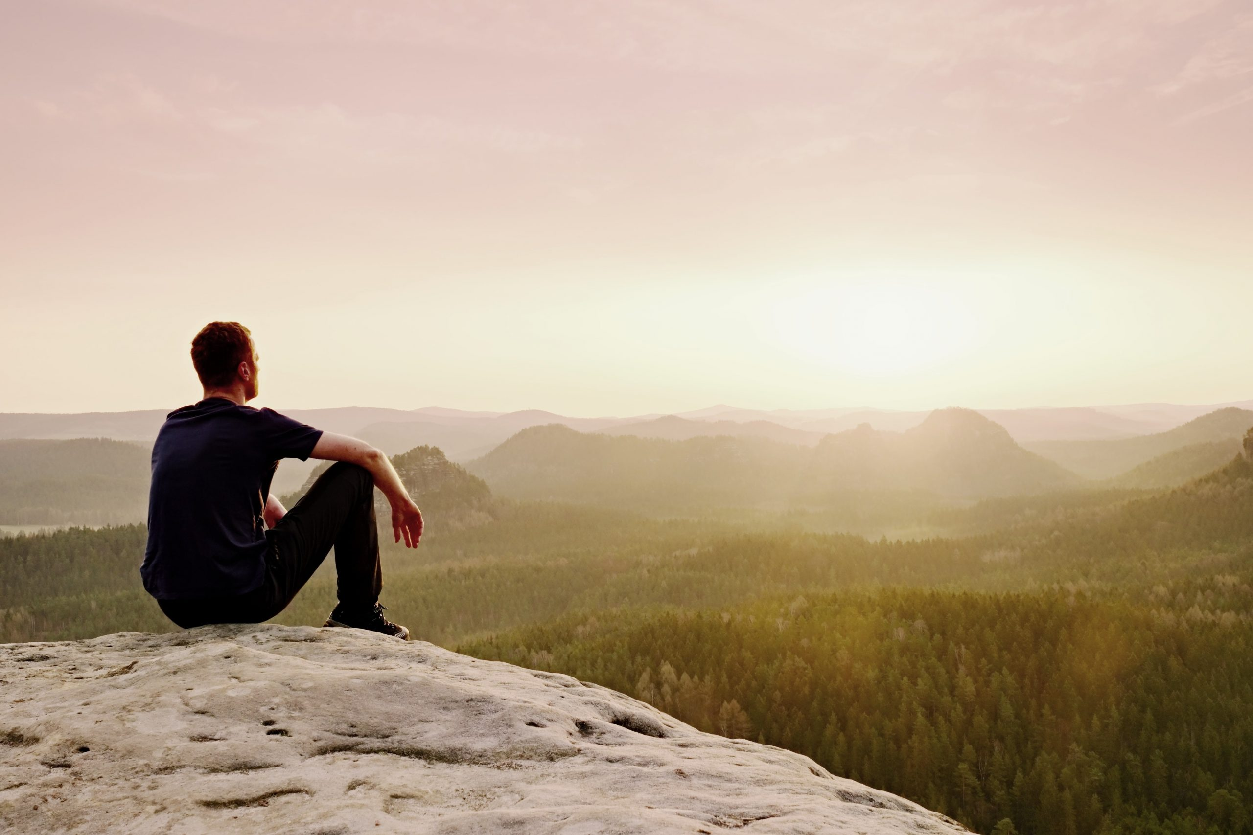 Man sitting on rock outcropping, resting and recharging in nature
