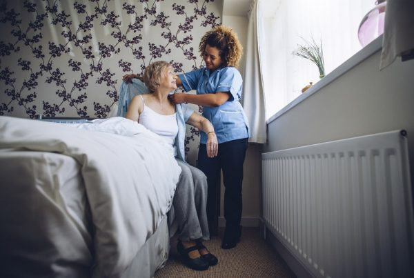 At home nurse helping female patient get out of bed, helping put on cardigan