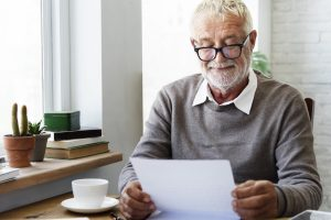 Elderly man sitting at table, reading a letter and smiling