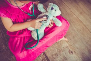 Little girl in pink dress playing doctor with stuffed bear