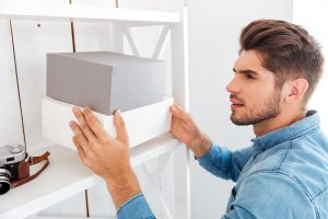 Young man putting away memory capsule box until determined date