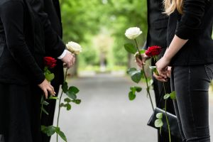Parents and two teenagers wearing black and carrying funeral roses