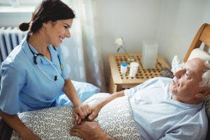 Nurse sitting at older mans' bedside, holding hand and smiling