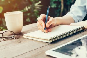 Person sitting at table outside, writing in notebook, expressing feelings