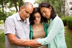 Mother, father, and teenage daughter praying together