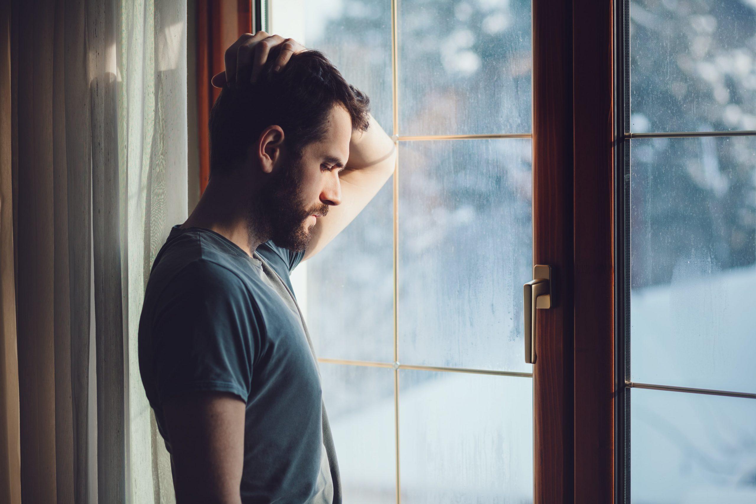 Shadowed man looking out window, hand on head, regretful