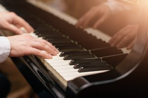 Person playing piano, focus on hands