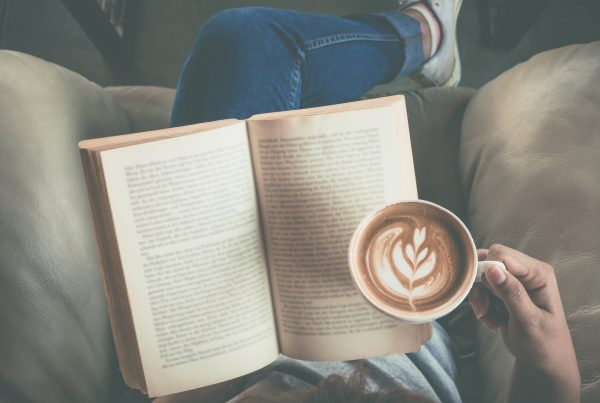 Person sitting on couch, reading and holding coffee