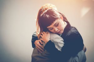 Female friends hug after a loss