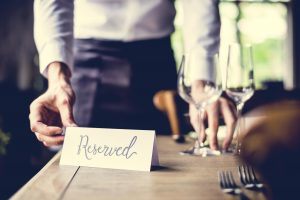 Waiter preparing a reserved table for a gathering