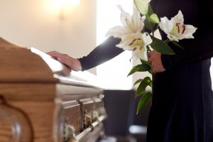 Woman standing next to casket, one hand touching top of casket and the other hand holding white lilies