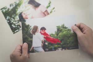 Hands holding photo of mother and child playing, reflecting on a cherished memory
