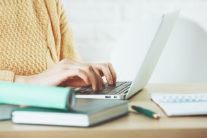 Woman sitting at computer, wearing yellow sweater, books on desk nearby