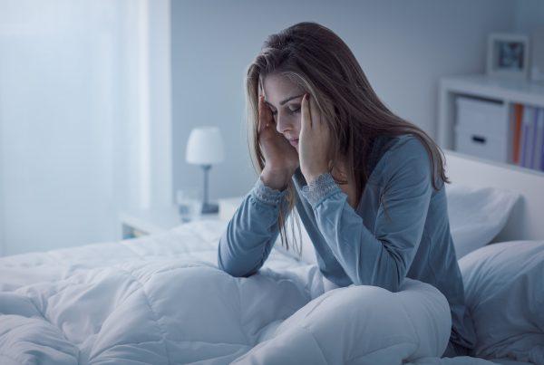 Woman sitting in bed in dark room, hands massaging temples, unable to sleep