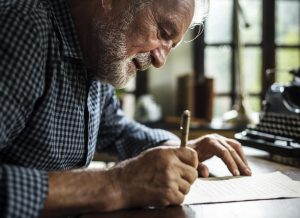 Elderly man handwriting an obituary