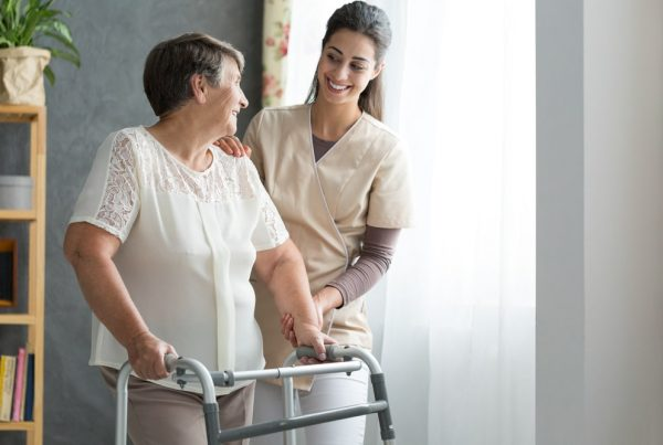 Nurse helping elderly woman move with walker