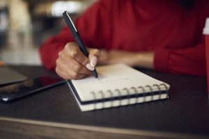 Woman sitting down, writing on notepad and wearing deep red sweater