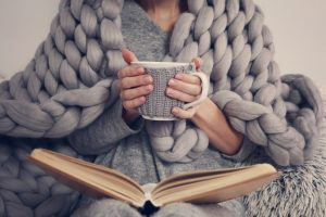 Woman wrapped in cozy blanket while holding mug and looking at photo album