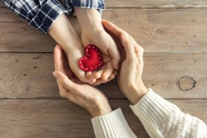 Parent cupping child's hands as child holds a red, cloth heart