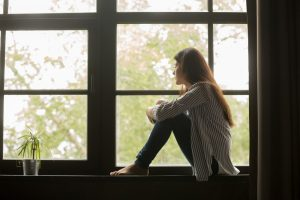 Young woman sitting on windowsill looking outside