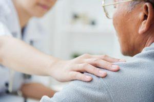 Female nurse putting comforting hand on elderly man's shoulder