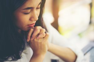 Teenage girl praying, hands clasped