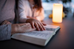 Mom and teenage daughter reading the Bible together, teenager touching mother's hand in a comforting way