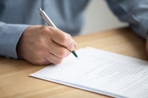 Man looking at document, pen poised to sign the bottom