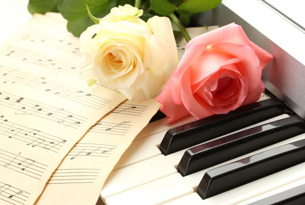 Two roses and music sheets laying on piano keys