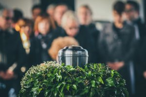 Mourners standing together and looking at a silver urn surrounded by greenery