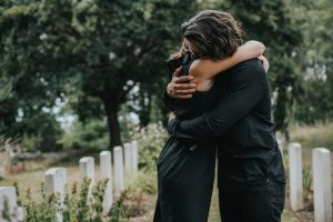 Man and woman wearing black standing in cemetery, hugging and expressing their grief