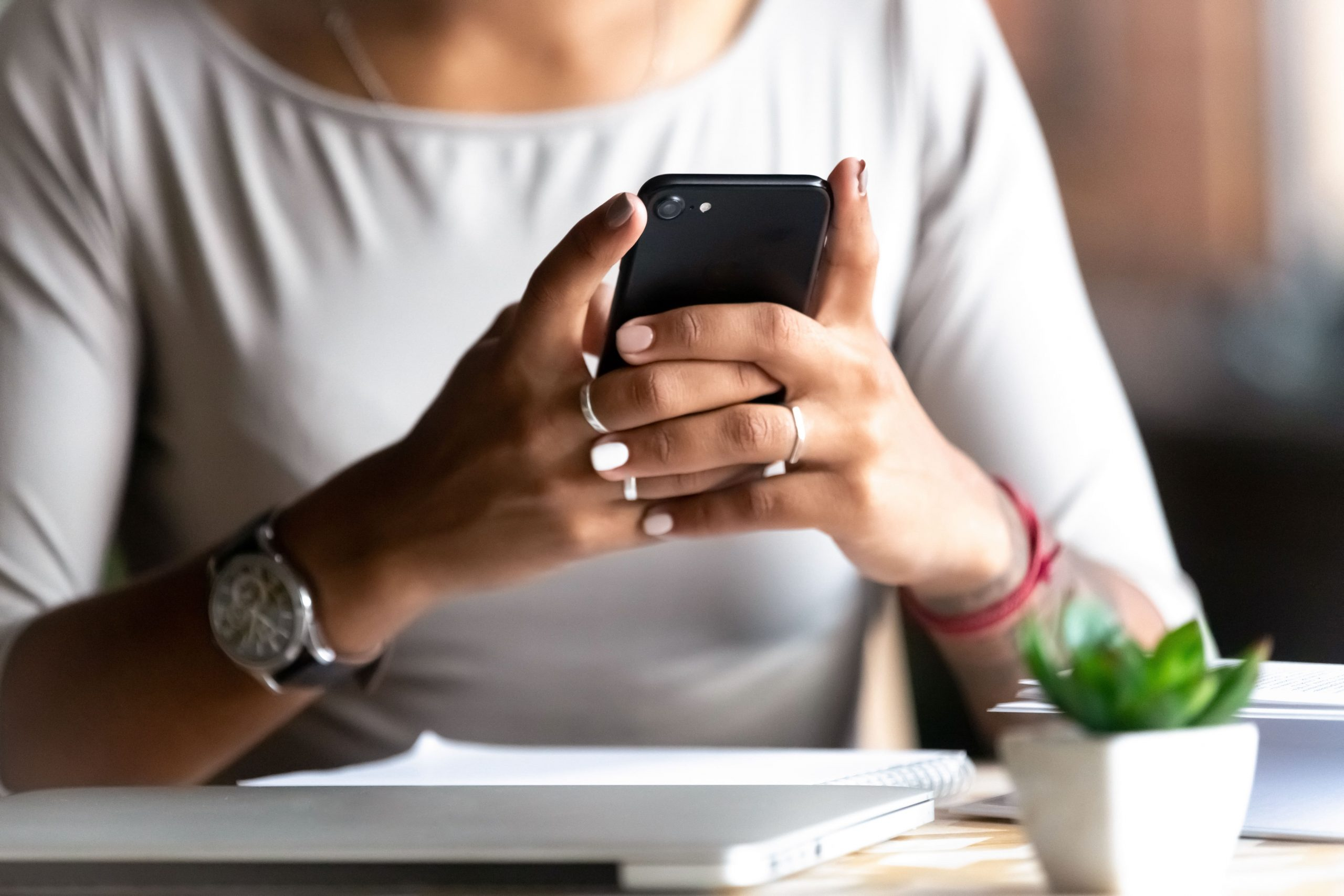 Woman sitting at her desk, holding phone in both hands as she looks at the screen