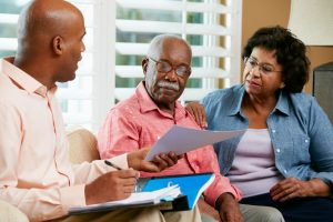Older couple sitting at home with funeral director, looking at documents, options, and pricing