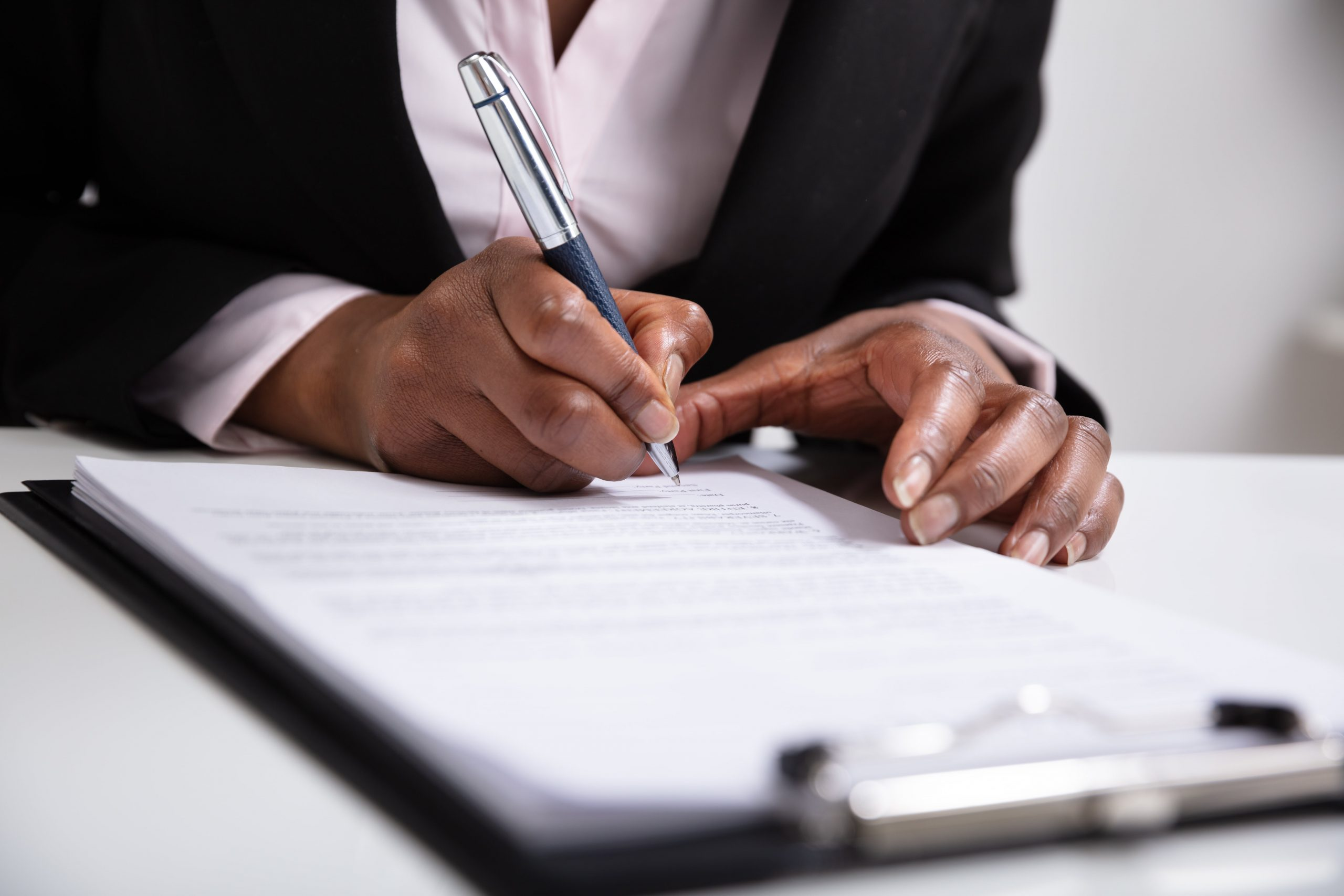 Focus on woman's hands as she signs documents on a clipboard