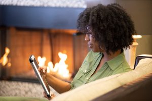 Woman sitting on couch near a fireplace, using her tablet