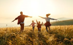 Family outside running in a field, enjoying the sunset