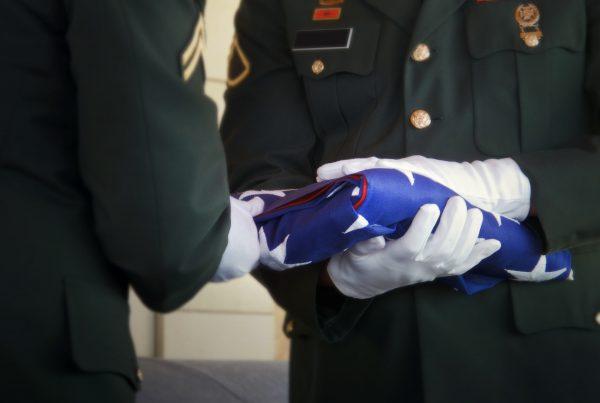 Two men in uniform folding the American flag
